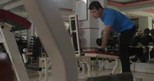 Στο νεαρό άνδρα γυμναστικής που κάνει την άσκηση για τα triceps φιλμ μικρού μήκους