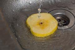 Στο νεροχύτη για έναν ψεκασμό του νερού και μια φέτα της κίτρινης Apple Στοκ Εικόνα
