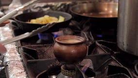 Στο δοχείο αργίλου σομπών με τη σούπα που βράζει, ο μάγειρας αφαιρεί το καυτό τηγάνι με τις λαβίδες απόθεμα βίντεο