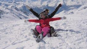 Στο πορτρέτο βουνών ενός ευτυχούς ζεύγους των σκιέρ που χαμογελούν και των όπλων αυξήσεων απόθεμα βίντεο