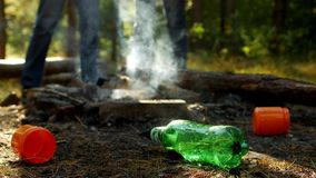 Στο πρώτο πλάνο σε ένα δασικό ξέφωτο υπάρχουν πλαστικά μπουκάλια των απορριμάτων, οι πυρκαγιές καπνίζουν, περίπατος ανθρώπων απόθεμα βίντεο
