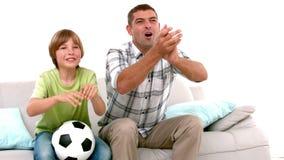 Στο σε αργή κίνηση ευτυχείς πατέρα και το γιο με το ποδόσφαιρο που προσέχουν τη TV απόθεμα βίντεο