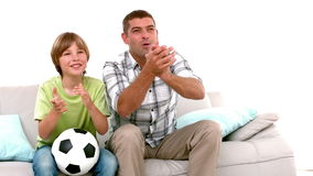 Στο σε αργή κίνηση ευτυχείς πατέρα και το γιο με το ποδόσφαιρο που προσέχουν τη TV φιλμ μικρού μήκους