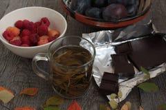 Στο σκοτεινό ξύλινο επιτραπέζιο καυτό πράσινο τσάι, σοκολάτα, μήλα, δαμάσκηνα, σμέουρο άνετο βράδυ φθινοπώρου ή χειμώνα Στοκ εικόνα με δικαίωμα ελεύθερης χρήσης