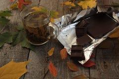 Στο σκοτεινό ξύλινο επιτραπέζιο καυτό πράσινο τσάι, σοκολάτα, μήλα, δαμάσκηνα, σμέουρο, βιβλίο βράδυ φθινοπώρου ή χειμώνα Στοκ εικόνα με δικαίωμα ελεύθερης χρήσης