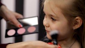Στο στούντιο ομορφιάς ενός μικρού κοριτσιού που κάνει ένα κούρεμα και που ισχύει makeup απόθεμα βίντεο