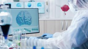 Στο σύγχρονο εργαστήριο ο επιστήμονας στη φόρμα δακτυλογραφεί στο πληκτρολόγιο υπολογιστών απόθεμα βίντεο