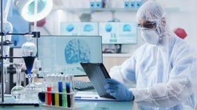 Στο σύγχρονο εργαστήριο ο επιστήμονας στη φόρμα εργάζεται σε ένα ψηφιακό PC ταμπλετών απόθεμα βίντεο