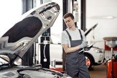 Στο τέλος της εργάσιμης ημέρας: νέος ένας automechanic εξετάζει τα αποτελέσματα της εργασίας του στοκ φωτογραφία