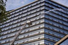 Στο τρυπάνι πυρκαγιάς, μια σκάλα μεγάλου υψομέτρου για να ψεκάσει την πυρκαγιά στα ψηλά κτίρια στοκ εικόνες