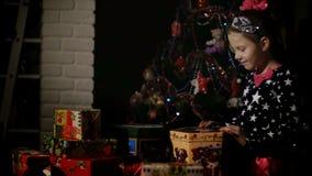 Στο λυκόφως της νύχτας, ένα αρκετά ξανθό κορίτσι με ένα ρόδινο τόξο στην τρίχα της, ένα όμορφο φόρεμα θαυμάζει απόθεμα βίντεο