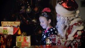 Στο λυκόφως της νύχτας, μεταξύ των δώρων στις φωτεινές ζωηρόχρωμες συσκευασίες εγγράφου, το αρκετά ξανθό κορίτσι με ένα ρόδινο τό φιλμ μικρού μήκους