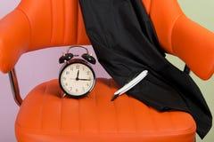 Στο υπόβαθρο της πορτοκαλιάς καρέκλας είναι ένα ξυπνητήρι, παρουσιάζει ο χρόνος, δίπλα στα στοιχεία για τα κουρέματα, ψαλίδι στοκ εικόνες