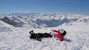 Στο χιονοδρομικό κέντρο βουνών ένα καλό ζεύγος των σκιέρ που παίζουν τις χιονιές απόθεμα βίντεο