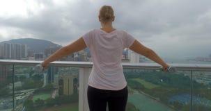 Στο Χονγκ Κονγκ, η Κίνα στο πεζούλι ένα νέο κορίτσι κάνει τις ασκήσεις με τους αλτήρες που διαδίδουν τα χέρια απόθεμα βίντεο