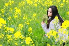 Στο όμορφο πρώιμο ελατήριο, μια νέα στάση γυναικών στη μέση των κίτρινων λουλουδιών βιασμών που αρχειοθετούνται που είναι η μεγαλ Στοκ Φωτογραφία