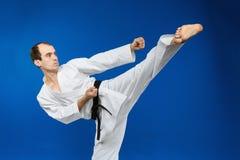 Στο karategi ο αθλητής κτυπά το λάκτισμα Στοκ Εικόνες