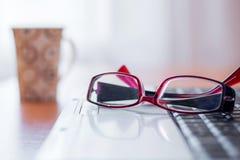 Στο lap-top γυαλιά, περαιτέρω στον πίνακα είναι ένα φλυτζάνι, στοκ εικόνες
