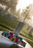 Στρατιωτικές κορδέλλες βραβείων και ετικέττες σκυλιών στην ταφόπετρα παλαιμάχων Στοκ Φωτογραφία