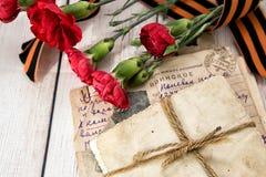 Στρατιωτική επιστολή, παλαιές φωτογραφίες, γαρίφαλα και κορδέλλα Gergiev στοκ φωτογραφίες