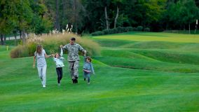 Στρατιωτικός πατέρας μπροστινής άποψης με το ευτυχές familiy περπάτημά του και το άλμα απόθεμα βίντεο
