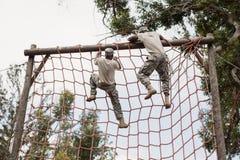 Στρατιωτικός στρατιώτης που αναρριχείται σε ένα δίχτυ κατά τη διάρκεια της σειράς μαθημάτων εμποδίων στοκ εικόνα