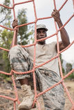 Στρατιωτικός στρατιώτης που αναρριχείται σε ένα δίχτυ κατά τη διάρκεια της σειράς μαθημάτων εμποδίων στοκ εικόνα με δικαίωμα ελεύθερης χρήσης