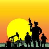 Στρατιώτες με τις πλατφόρμες άντλησης πετρελαίου στο υπόβαθρο Στοκ Εικόνες