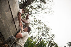 Στρατιώτες που βοηθούν το άτομο για να αναρριχηθεί στον ξύλινο τοίχο στοκ εικόνες