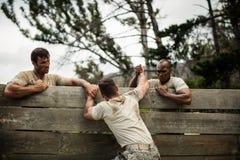 Στρατιώτες που βοηθούν το άτομο για να αναρριχηθεί στον ξύλινο τοίχο στοκ εικόνα με δικαίωμα ελεύθερης χρήσης