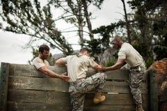 Στρατιώτες που βοηθούν το άτομο για να αναρριχηθεί στον ξύλινο τοίχο στοκ εικόνα