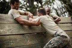 Στρατιώτες που βοηθούν το άτομο για να αναρριχηθεί στον ξύλινο τοίχο στοκ φωτογραφία με δικαίωμα ελεύθερης χρήσης