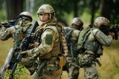 Στρατιώτες που στέκονται με τα όπλα και τα βλέμματα πίσω Στοκ φωτογραφία με δικαίωμα ελεύθερης χρήσης