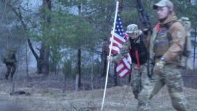 Στρατιώτες στην κάλυψη με τα όπλα αγώνα και στις ΗΠΑ στη δασική, στρατιωτική έννοια φιλμ μικρού μήκους