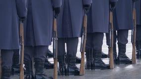 Στρατιώτες στις μπλε στολές και τις μαύρες μπότες, που κρατούν ένα πυροβόλο όπλο και που στέκονται σε μια γραμμή φιλμ μικρού μήκους