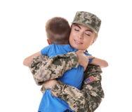 Στρατιώτης γυναικών που αγκαλιάζει με το γιο στο υπόβαθρο Στοκ φωτογραφία με δικαίωμα ελεύθερης χρήσης