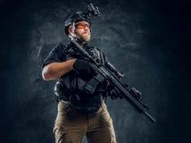 Στρατιώτης ειδικών δυνάμεων που φορά τη πανοπλία και το κράνος με τη νυχτερινή όραση που κρατά ένα επιθετικό τουφέκι Φωτογραφία σ στοκ εικόνες με δικαίωμα ελεύθερης χρήσης