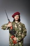 Στρατιώτης με το περίστροφο ενάντια σε γκρίζο Στοκ Φωτογραφίες