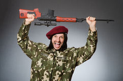 Στρατιώτης με το περίστροφο ενάντια σε γκρίζο Στοκ εικόνα με δικαίωμα ελεύθερης χρήσης