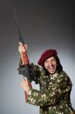 Στρατιώτης με το περίστροφο ενάντια σε γκρίζο Στοκ φωτογραφίες με δικαίωμα ελεύθερης χρήσης