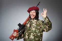 Στρατιώτης με το περίστροφο ενάντια σε γκρίζο Στοκ Εικόνες