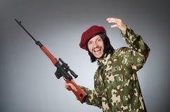 Στρατιώτης με το περίστροφο ενάντια σε γκρίζο Στοκ εικόνες με δικαίωμα ελεύθερης χρήσης