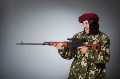 Στρατιώτης με το περίστροφο ενάντια σε γκρίζο Στοκ Φωτογραφία