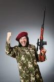 Στρατιώτης με το περίστροφο ενάντια σε γκρίζο Στοκ Εικόνα