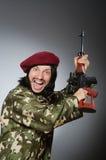 Στρατιώτης με το περίστροφο ενάντια σε γκρίζο Στοκ φωτογραφία με δικαίωμα ελεύθερης χρήσης