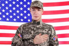 Στρατιώτης με το χέρι στην καρδιά ενάντια στη σημαία Στοκ εικόνα με δικαίωμα ελεύθερης χρήσης