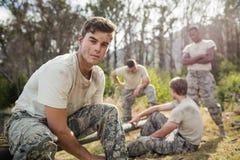 Στρατιώτης που δένει τις δαντέλλες παπουτσιών του στο στρατόπεδο μποτών Στοκ Εικόνες