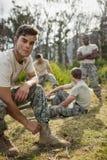 Στρατιώτης που δένει τις δαντέλλες παπουτσιών του στο στρατόπεδο μποτών Στοκ Φωτογραφίες