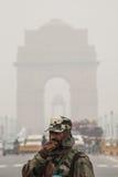 Στρατιώτης που βήχει στην αιθαλομίχλη με την πύλη της Ινδίας πίσω Στοκ φωτογραφία με δικαίωμα ελεύθερης χρήσης