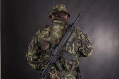 Στρατιώτης στην κάλυψη και το σύγχρονο όπλο M4 Στοκ Εικόνες